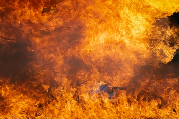 Chama ardente do fogo com óleo de combustível, gasolina que queima-se sobre o recipiente, fumo e poluição do fogo
