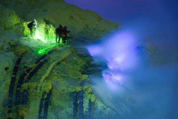 Chama azul na mineração do enxofre na noite, vulcão de kawah ijen, east java, indonésio.