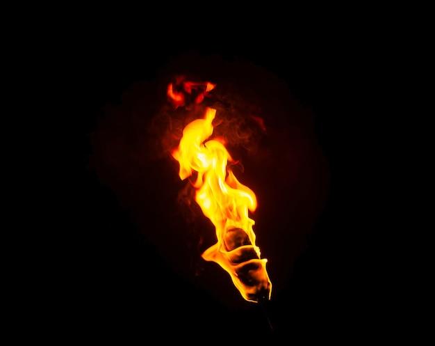Chama de uma tocha no escuro em um fundo preto, apenas o fogo é visível