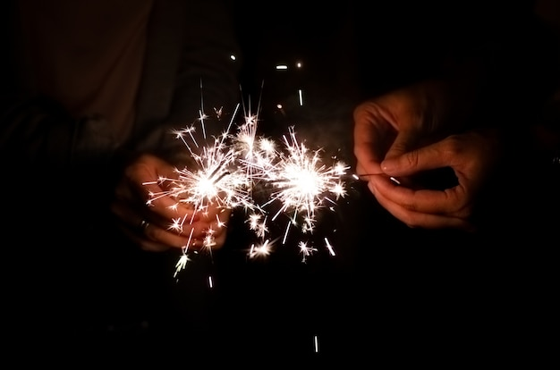 Chama luz de diamante brilhando nas mãos de mulher amigo segurando no fundo da noite