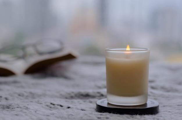 Chama queimando uma vela de aroma turva para relaxar ao ler um livro em casa no inverno. zen e relaxe o conceito.