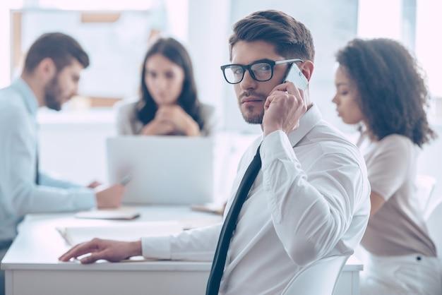Chamada de negócios importante. jovem bonito de óculos falando no celular e olhando para a câmera enquanto está sentado à mesa do escritório com seus colegas de trabalho