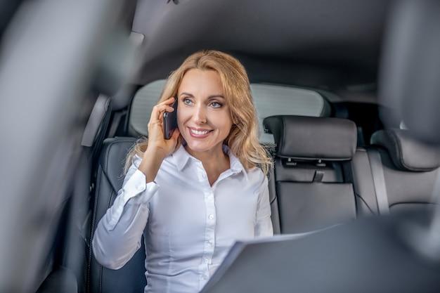 Chamada de negócios. mulher loira falando ao telefone em um carro e parecendo envolvida