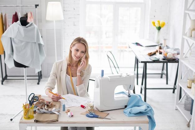 Chamada de negócios. uma artesã bem-sucedida fazendo um esboço de desenho enquanto fala ao telefone