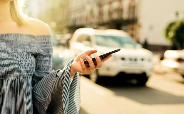 Chamada de táxi online. mulher jovem e atraente pede um táxi usando um aplicativo móvel em uma estrada movimentada da cidade