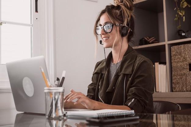 Chamada de videoconferência on-line inteligente, trabalho remoto, trabalho remoto, atividade de escritório em casa, com uma bela mulher de meia-idade desfrutando de tecnologia moderna on-line e conexão à internet gratuita