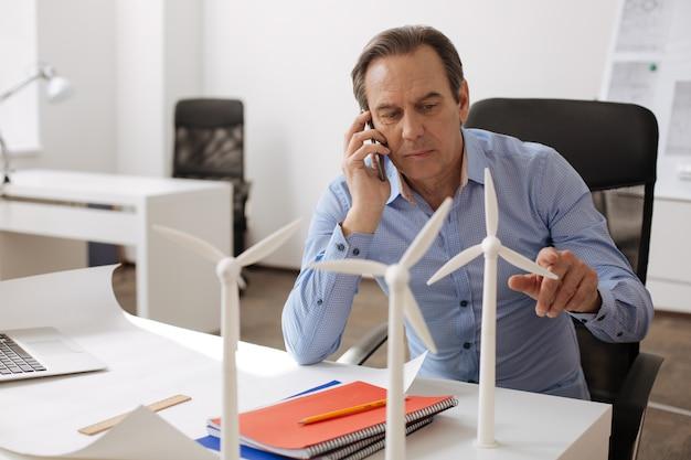 Chamada importante. engenheiro profissional sério sentado à mesa e falando no telefone inteligente, enquanto trabalhava na construção de turbinas ecológicas