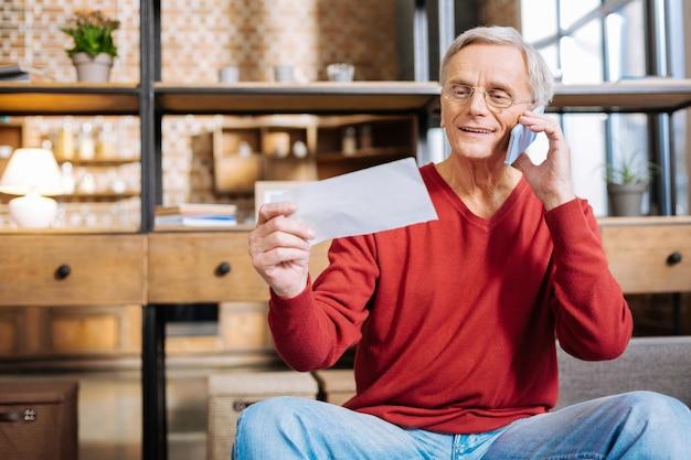 Chamada importante. homem bonito simpático positivo sorrindo e falando ao telefone enquanto olha para a nota