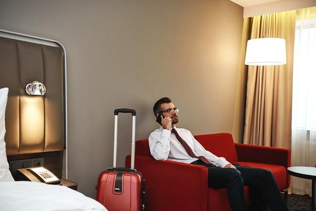 Chamada importante. homem de negócios de óculos com mala e tablet sentado no sofá do quarto do hotel