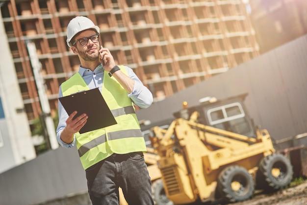 Chamada importante para jovem engenheiro civil ou supervisor de construção usando capacete falando por telefone