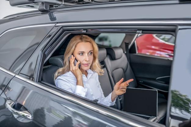 Chamada telefónica. mulher loira sentada em um carro e falando ao telefone
