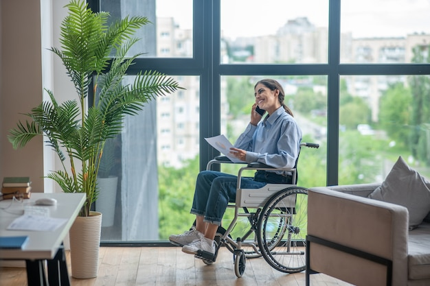 Chamada telefónica. uma linda garota em uma cadeira de rodas falando ao telefone e sorrindo