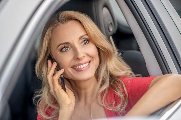 Chamada telefónica. uma linda mulher com um vestido vermelho falando ao telefone e sorrindo