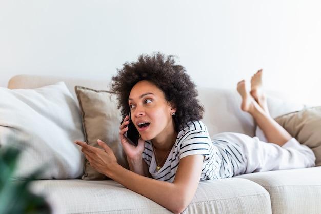 Chamador feliz jovem falando em seu telefone celular em casa