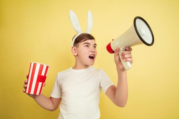 Chamando com trombeta, pipoca. menino caucasiano como um coelhinho da páscoa em fundo amarelo. saudações de páscoa feliz.