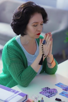 Chamando por espíritos. cartomante poderoso e sério fechando os olhos enquanto chamando espíritos