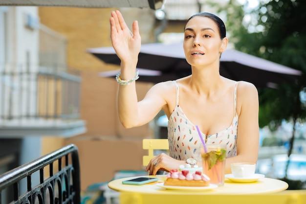 Chamando um garçom. bela jovem sentada à mesa ao ar livre e levantando a mão enquanto chama um garçom
