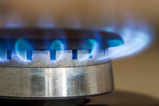 Chamas azuis de gás natural queima no fogão da cozinha, fechar foto com dof raso