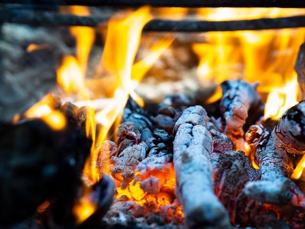 Chamas brilhantes de fogo e brasas na fogueira
