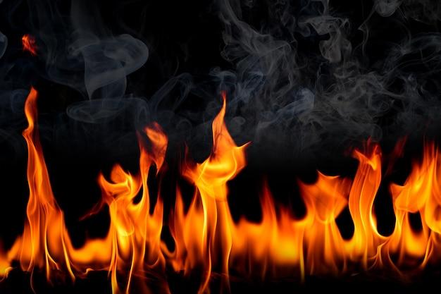 Chamas de fogo com fumaça sobre fundo preto.