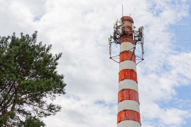 Chaminé branca vermelha com instalação de aço no topo com árvore no céu azul