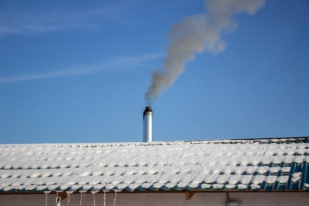 Chaminé de aço moderna de uma sauna russa coberta de neve contra um céu azul.