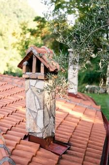 Chaminé de pedra em um telhado de telhas contra um fundo de galho de árvore verde