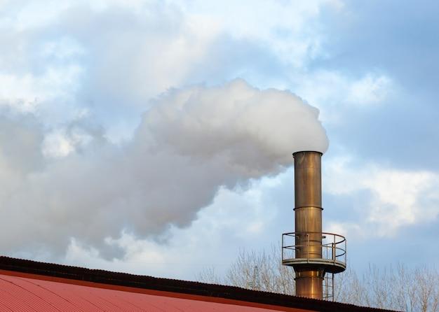 Chaminé de uma fábrica, processo industrial que produz fumaça branca.