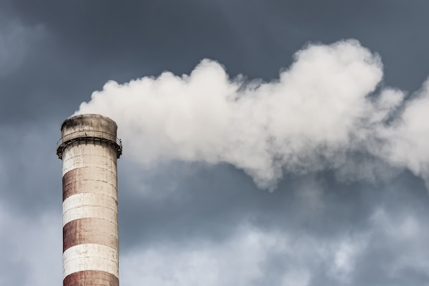 Chaminé industrial de fumo em nuvens escuras. conceito de proteção ambiental