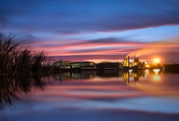 Chaminé longa da fábrica do açúcar do nascer do sol da paisagem da exposição na fábrica, poluição.