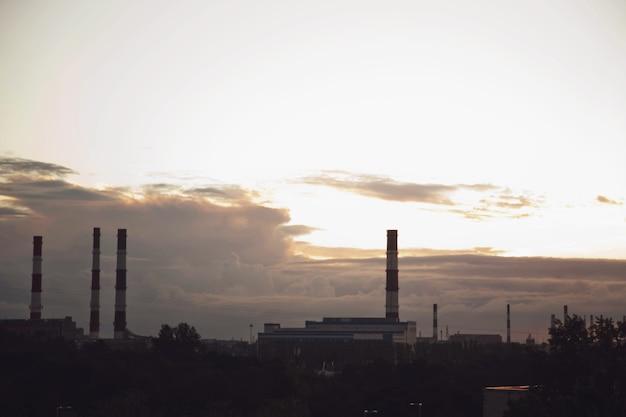 Chaminés de tijolos industriais contra o céu do sol texturizado. conceito de produção e poluição ambiental na metrópole. bandeira texturizada de fundo de cidade. copie o espaço para o site