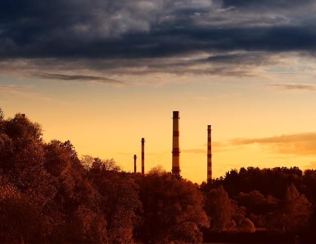 Chaminés industriais cobertas por um fundo de nuvens cinzentas