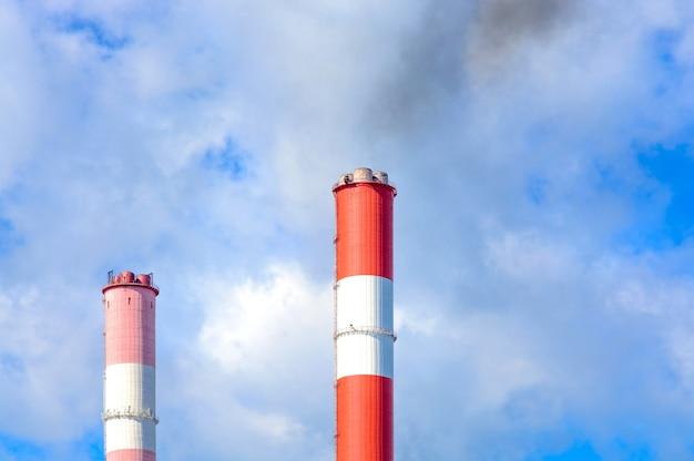 Chaminés industriais com fumaça contra o céu azul com nuvens