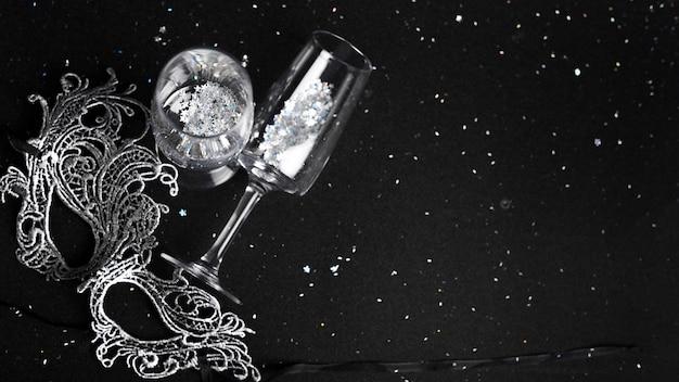 Champagne flutes decorados com brilhos perto de máscara de carnaval