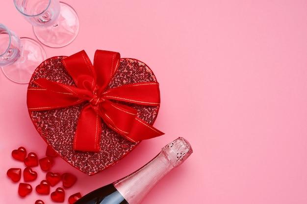 Champanhe, copos e caixa de presente em forma de coração com uma fita vermelha na mesa-de-rosa. conceito de dia dos namorados vista superior.