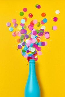 Champanhe de natal azul pintado com confete de glitter enquanto uma bebida borbulha em um fundo amarelo, copie o espaço. postura plana.