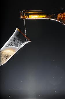 Champanhe, derramando em vidro em fundo preto