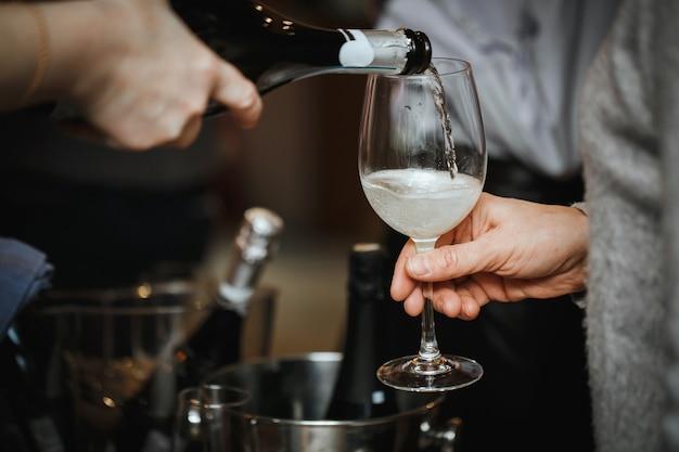 Champanhe é despejado em um copo para o visitante.