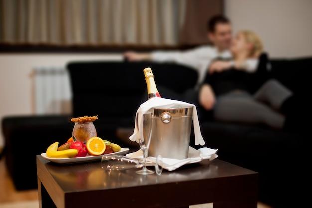 Champanhe e frutas na mesa. casal se beijando no sofá