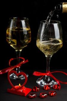 Champanhe é servido em copos em uma superfície preta ao lado de um castiçal em forma de coração com uma vela acesa e uma caixa com um anel