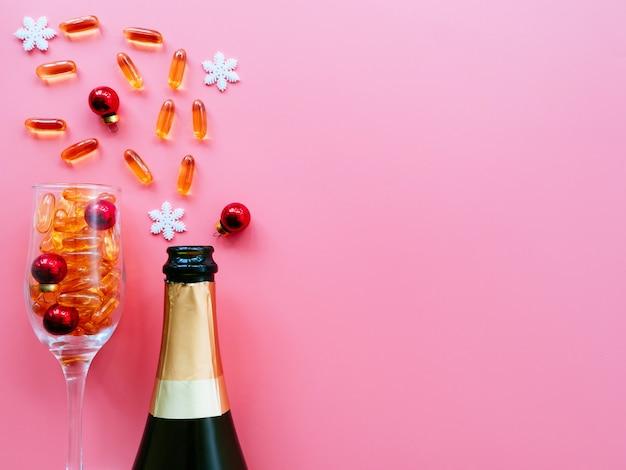 Champanhe e taças cheias de pílulas e brinquedos de natal