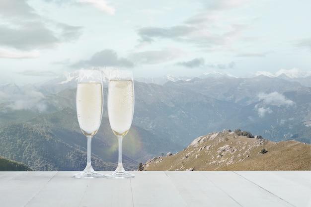Champanhe em taças e paisagem de montanhas no fundo. bebida de álcool e aparência de neve e céu nublado na frente dele. quente no dia de inverno, feriados, viagens, aventuras, tempo de celebração.