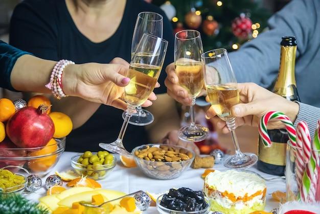Champanhe na mão contra a árvore de natal