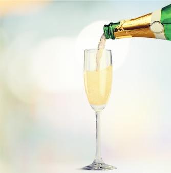 Champanhe servindo na taça em um fundo de bokeh claro desfocado