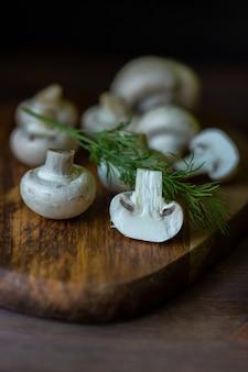 Champignon de cogumelos crus em uma placa de madeira no escuro