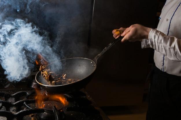 Champignon de vista lateral fritando com fumaça e fogo e humanos no fogão