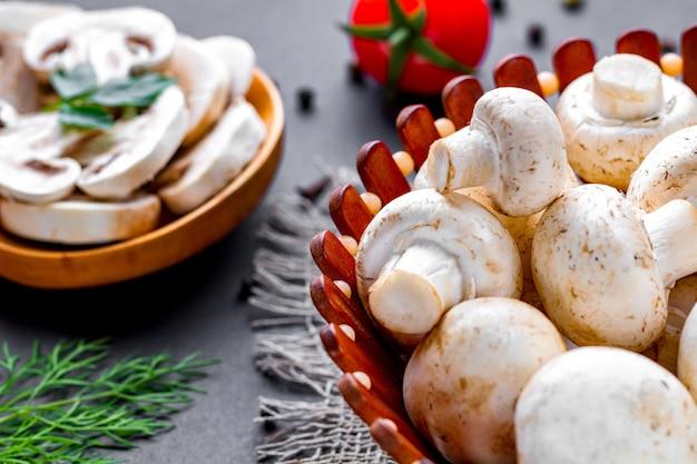 Champignon fatiado fresco na colher de pau. cozinhar pratos caseiros de cogumelos brancos maduros com salsa, endro e tomate cereja