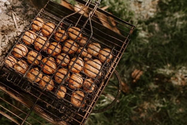 Champignons de cogumelos redondos pequenos e idênticos brancos empilhados em fileiras iguais em um churrasco na grelha.