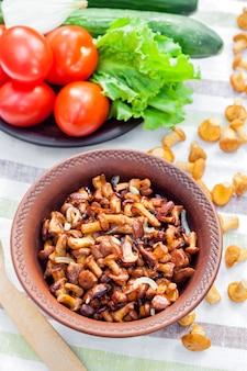 Chanterelles fritos com cebola em uma tigela rústica e prato com legumes frescos para salada