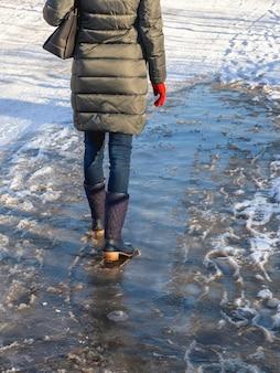 Chão com crosta de gelo, uma mulher caminhando em uma rua escorregadia, clima de primavera. condições geladas. visão vertical.